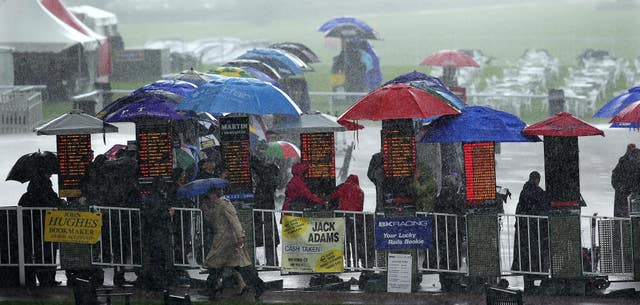 Racegoers try to keep dry as heavy rain falls during a race meeting at York Racecourse (John Giles/PA)