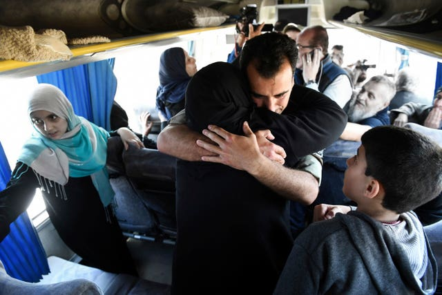 A Syrian government soldier hugs a woman inside a bus carrying released families  (SANA via AP)