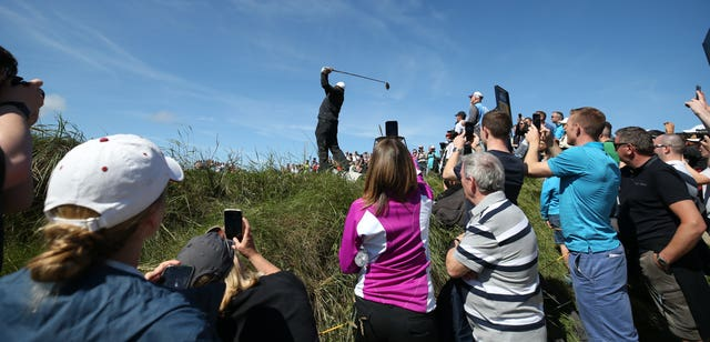Spectators take photos of Woods as he tees off at the ninth hole at Portrush