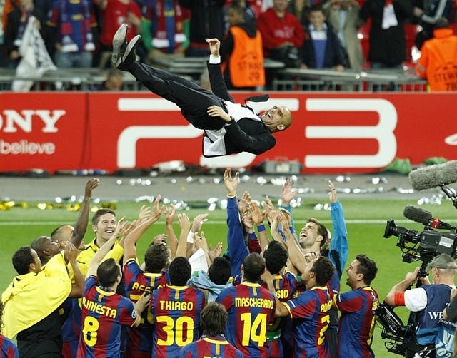 Barcelona's players celebrate by throwing their manager Pep Guardiola up in the air. (PA)