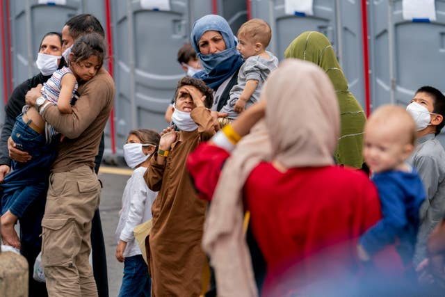 People evacuated from Afghanistan step off a bus as they arrive at a processing centre i (Andrew Harnik/AP)