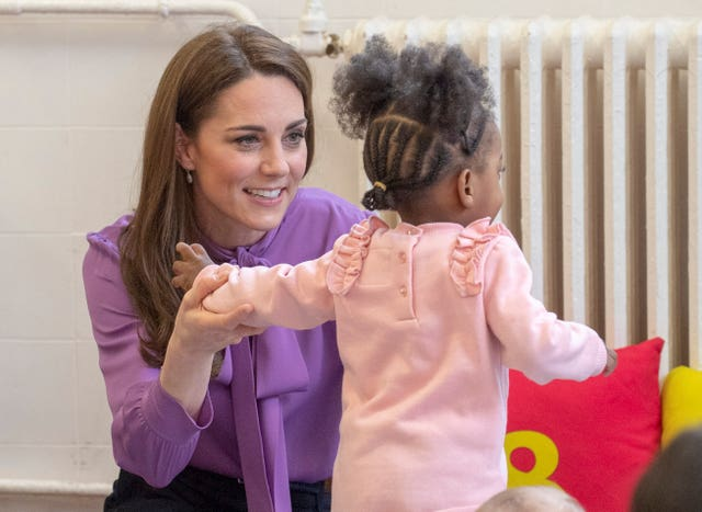 Kate plays with a child during her visit to the children's centre