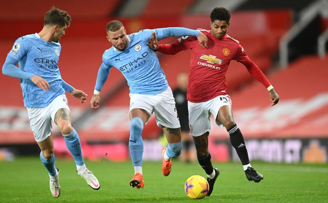 Marcus Rashford battles for the ball with Kyle Walker