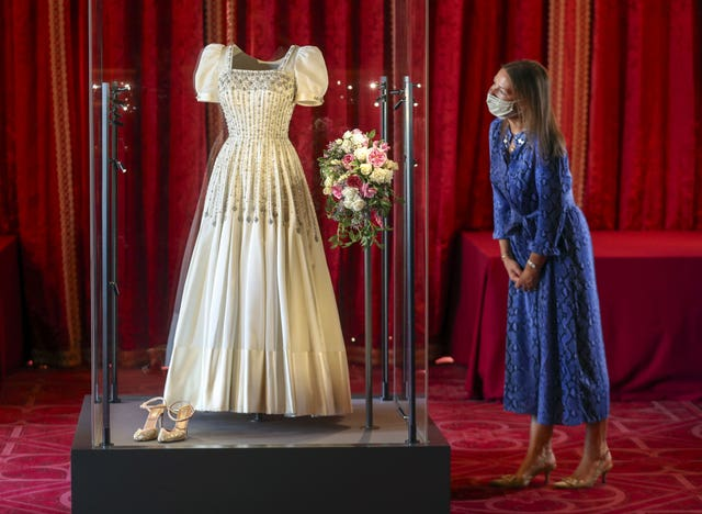 Royal Collection Trust Curator Caroline de Guitut looks at Princess Beatrice's wedding dress which will go on public display at Windsor Castle from Thursday. Steve Parsons/PA Wire