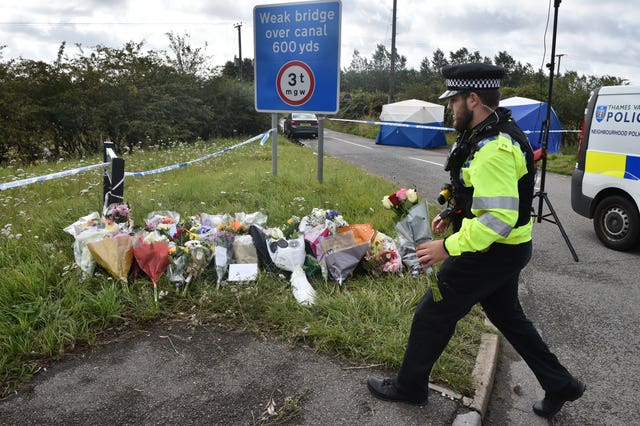A police officer lays a floral tribute at the scene