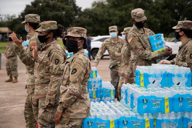 National Guard soldiers distribute bottled water to residents after contamination of the water supply
