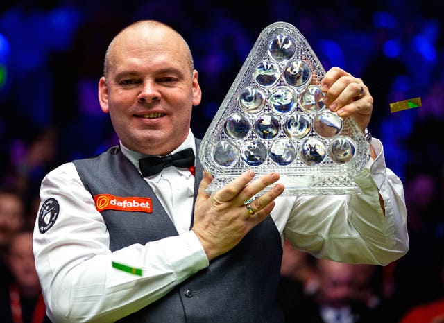 Stuart Bingham celebrates winning the Masters with the Paul Hunter trophy