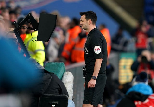 Referee Andrew Madley checks the VAR screen before rescinding a red card shown to Crystal Palace's Joel Ward against Sheffield United