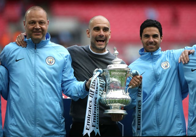 Mikel Arteta, right, celebrates alongside Pep Guardiola, centre, with the FA Cup