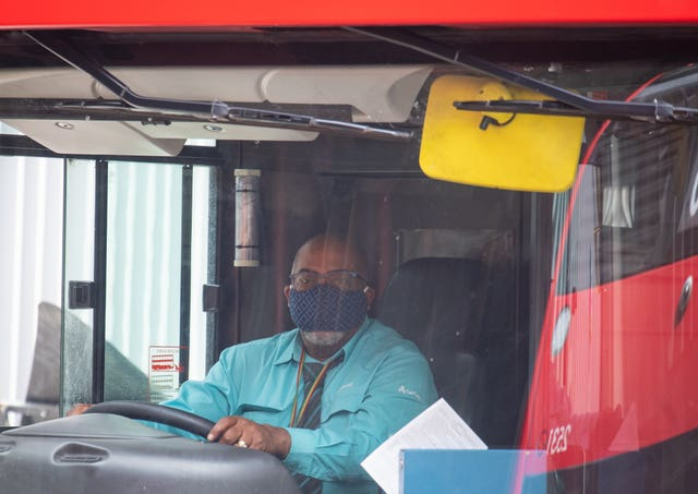 A London bus driver wearing a protective face mask (Dominic Lipinski/PA)