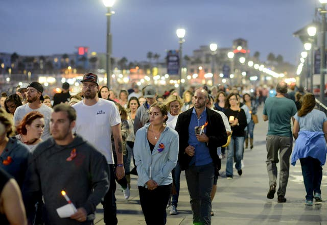 A 200-strong procession walk silently along Huntington Beach Pier in California. A candlelight vigil honouring those who died in the mass shooting was held Sunday evening at Huntington Beach's Pier Plaza. (Cindy Yamanaka/The Orange County Register/AP)