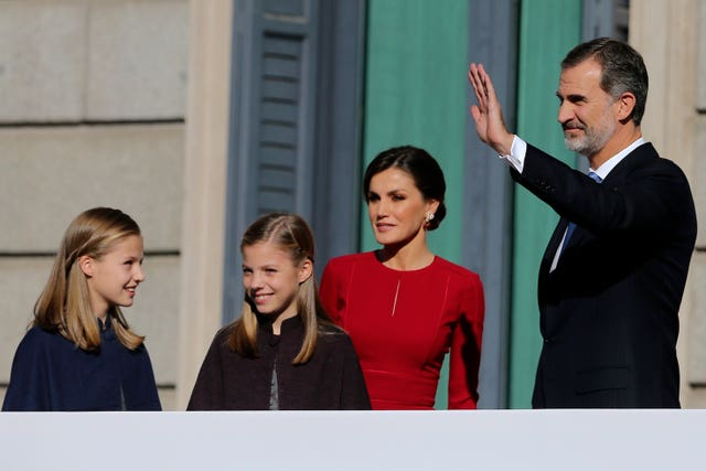 Spain's King Felipe VI and his wife Queen Letizia wave to the crowd with their daughters Princess Leonor, left, and Princess Sofia