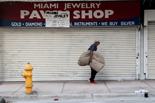 A homeless man carrying his bedding walks past the Miami Jewelry Pawn Shop