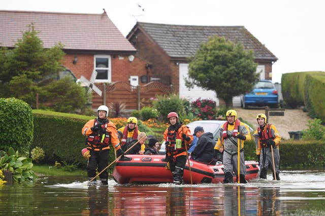 Residents are taken to safety in an inflatable boat by rescue workers in Wainfleet (Joe Giddens/PA)