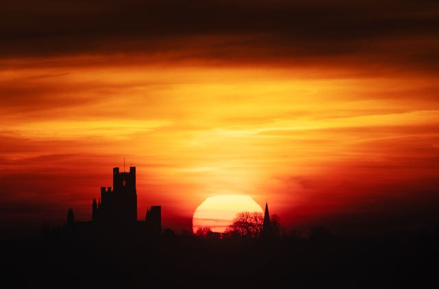 The sun rises behind Ely Cathedral in The Fens