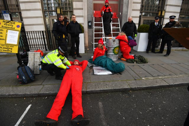 Police officers search an activist outside BP's headquarters