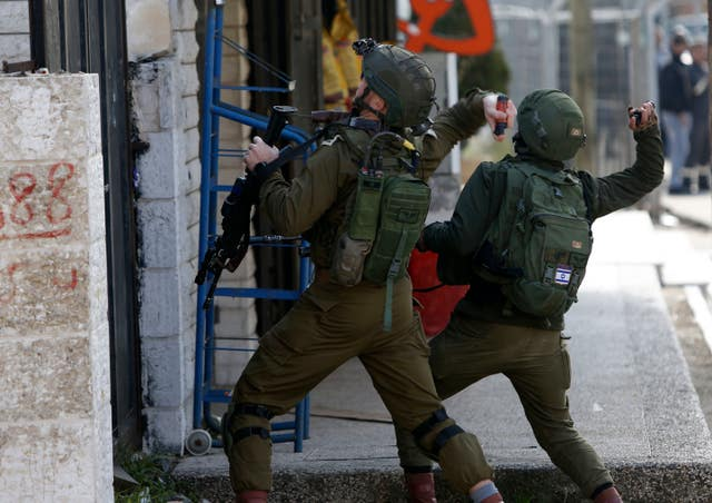 Israeli soldiers clash with Palestinians during a search for suspects