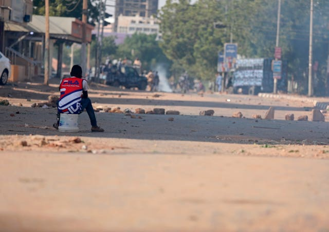 A protester sits in a street facing security forces (Marwan Ali/AP)
