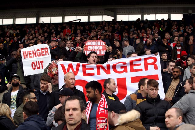 Fans hold up a Wenger Out banner