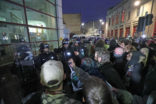 Police hold back people outside Bridewell police station in Bristol