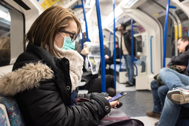 A woman wearing a facemask on the London Underground