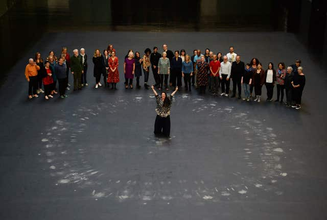 Tania Bruguera, centre, and guests stand after lying on her artwork, a heat sensitive floor, in the Turbine Hall