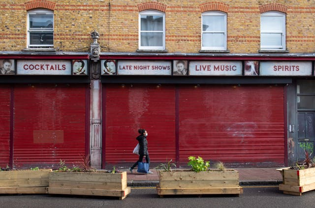 A woman passes a shuttered bar in Brixton, south London, at the start of the first full week of the four-week national lockdown in England (Dominic Lipinski/PA)