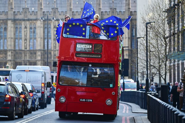 Remain supporters on board an open-top bus outside the Houses of Parliament