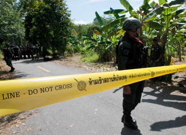 Thai police secure the road leading to the shooting scene