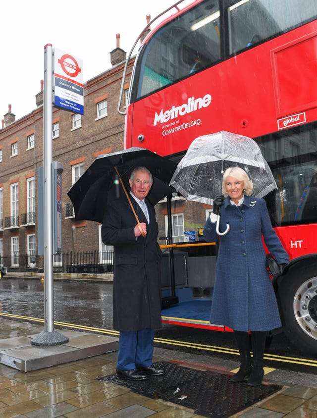 The Prince of Wales and Duchess of Cornwall prepare to board a new electric double decker bus at Clarence House in London to travel to the London Transport Museum