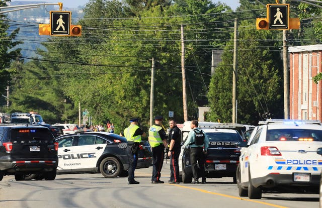 Police officers survey the area of a shooting in Fredericton, New Brunswick, Canada