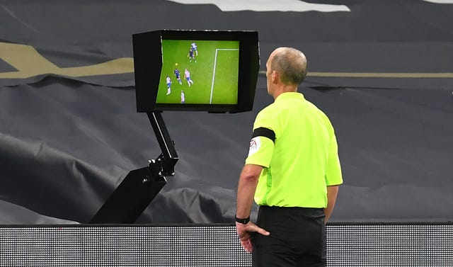 Referee Mike Dean consults the VAR screen before disallowing a goal for Manchester City's Aymeric Laporte