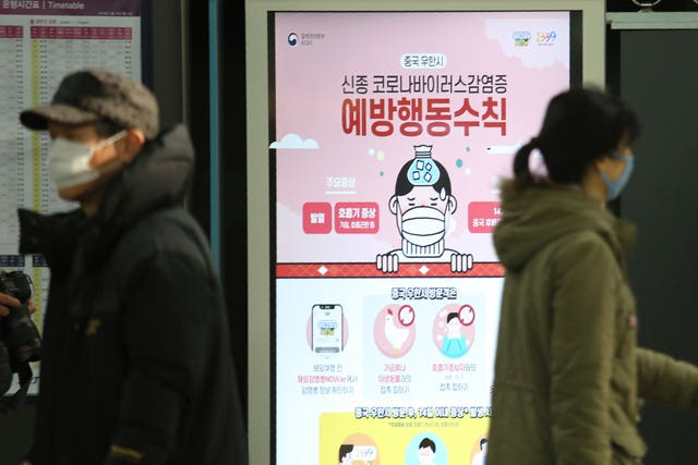 People walk past a poster warning about a new coronavirus at Suseo Station in Seoul, South Korea