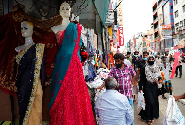 A Sri Lankan Muslim woman walks in a busy street (Eranga Jayawardena/AP)