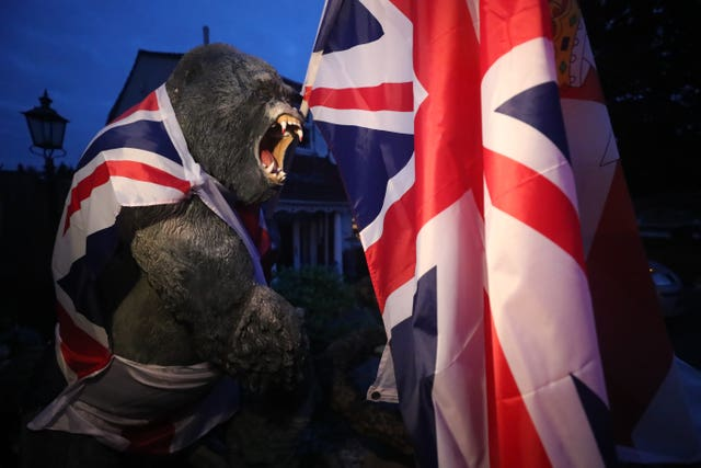 A plastic gorilla is wrapped in Union flag by a bonfire on Belfast's Shankill Road