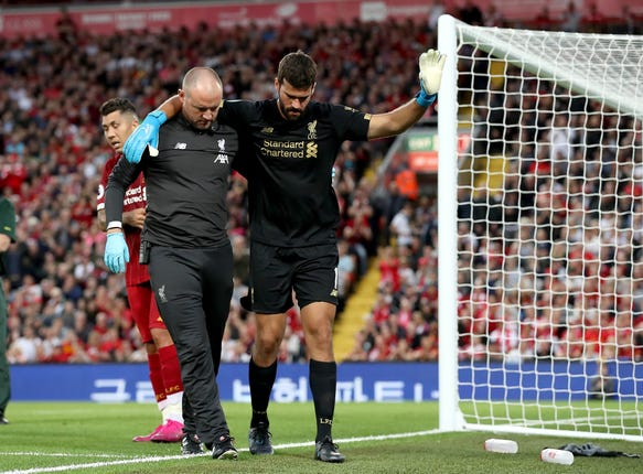 Liverpool goalkeeper Alisson leaves the pitch after picking up an injury