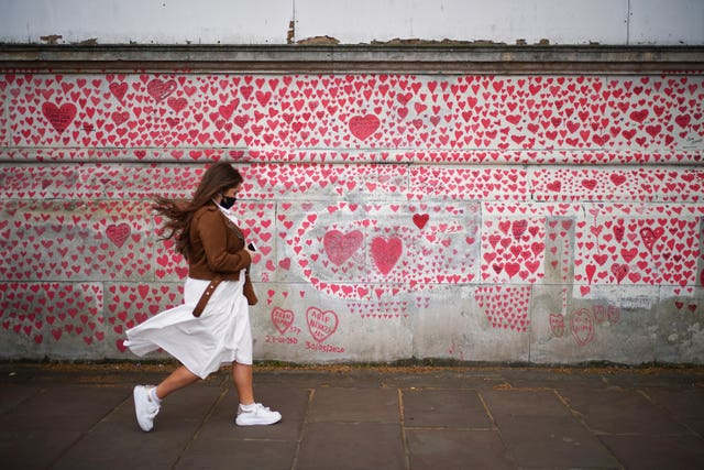 A woman walks past the National Covid Memorial Wall on the Embankment in London (Yui Mok/PA)