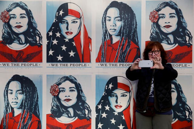 A protester takes a selfie in front of posters supporting the cause in Los Angeles