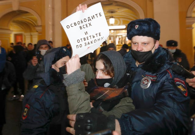 Police officers detain a supporter of opposition leader Alexei Navalny during a rally in St Petersburg