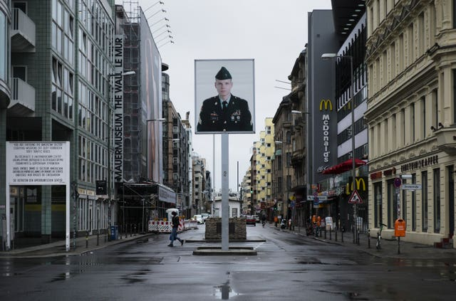 Only very few people walk on the Friedrichstrasse near the former Checkpoint Charlie, an allied border crossing during the Cold War, in Berlin, Germany (Markus Schreiber/AP)