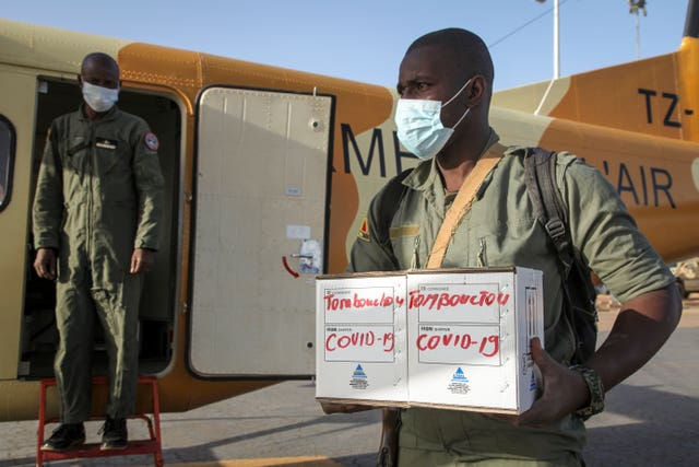 A Malian soldier in the capital Bamako carries samples from patients in Timbuktu to a military plane (Baba Ahmed/AP)