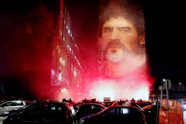 Fans light flares as they gather under a mural depicting Diego Maradona in Naples