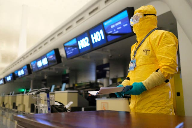 A worker in a protective suit holds paperwork before an evacuation flight for EU nationals at Wuhan Tianhe International Airport in Wuhan in central China's Hubei Province