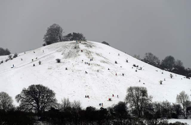 People enjoy a snow covered hill near Princes Risborough, Buckinghamshire, following a weekend wintry blast in December (Steve Parsons/PA)