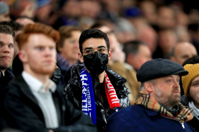A football fan wearing a face mask in the crowd of a match