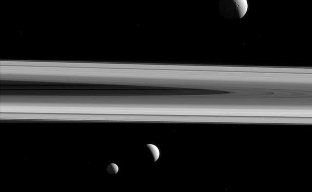 Three of Saturn's moons - Tethys, above, Enceladus, second left, and Mimas, seen from the Cassini spacecraft
