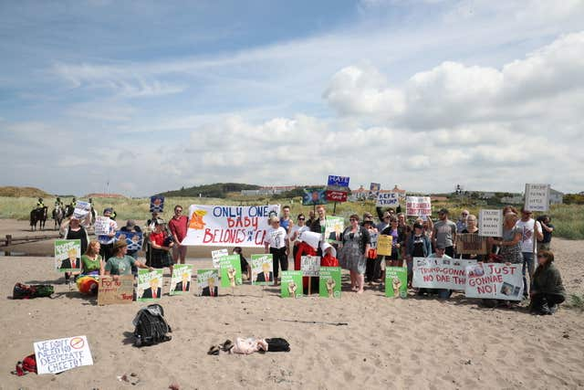 Crowds protest on a beach near the course