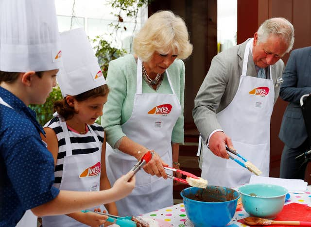 Camilla and Charles donned aprons to take part in a cooking activity at the hospital (Phil Noble/PA)