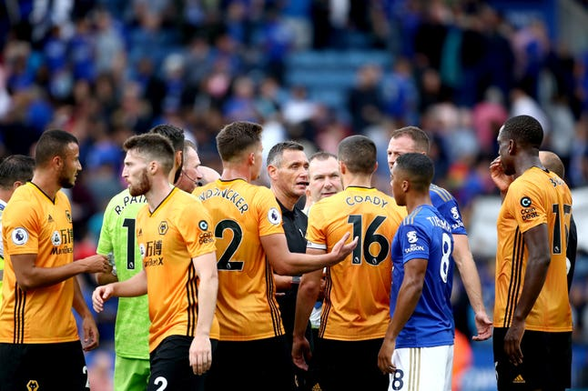 Wolves surround referee Andre Marriner at the end of the match after VAR ruled out a goal against Leicester