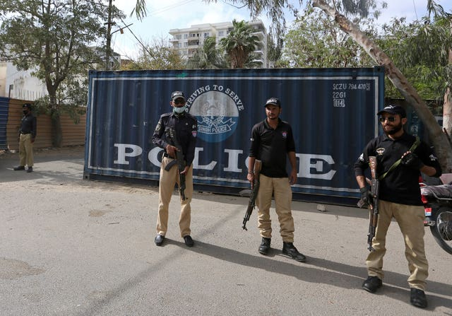 Police officers guard a road blocked with shipping containers, near the French consulate, in Karachi, Pakistan (Fareed Khan/AP)